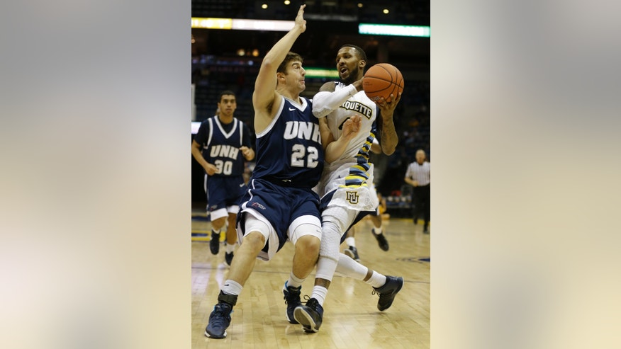 Marquette's Todd Mayo, right, drives against and New Hampshires' Scott Morris (22) during the first half of an NCAA college basketball game Thursday, Nov. 21, 2013, in Milwaukee. (AP Photo/Jeffrey Phelps)