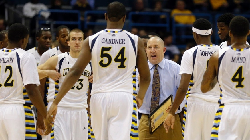 Marquette Head coach Buzz Williams gathers his team during a timeout against New Hampshire during the first half of an NCAA college basketball game Thursday, Nov. 21, 2013, in Milwaukee. (AP Photo/Jeffrey Phelps)