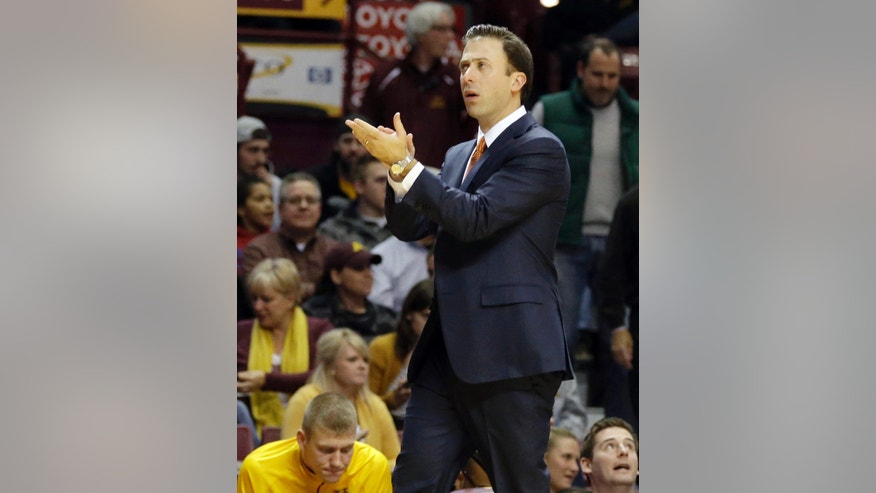 ADVANCE FOR WEEKEND EDITIONS, NOV 23-24 - FILE - In this Nov. 12, 2013 file photo, new Minnesota head basketball coach Richard Pitino, the son of Hall of Fame coach Rick Pitino, applauds his team in the first half of an NCAA college basketball game against Montana in Minneapolis. Pitino, roughly 10 years older than his players, brings a fast-paced offense and full-court defense to the Gophers team. (AP Photo/Jim Mone, File)