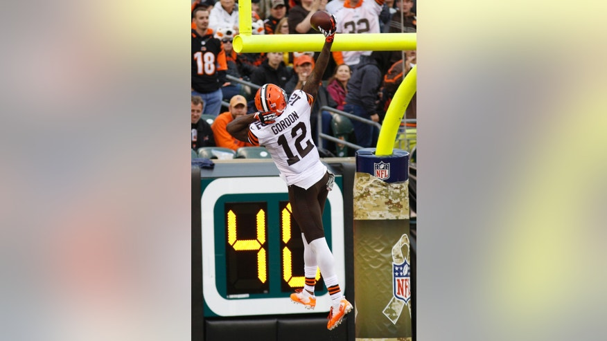 Cleveland Browns wide receiver Josh Gordon (12) spikes the ball over the goalpost after scoring on a 74-yard pass reception against the Cincinnati Bengals in the second half of an NFL football game on Sunday, Nov. 17, 2013, in Cincinnati. (AP Photo/David Kohl)