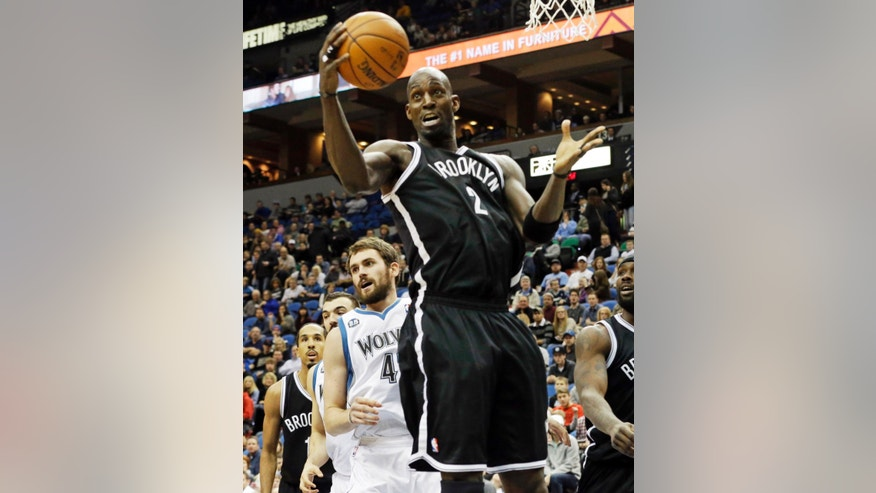 Brooklyn Nets' Kevin Garnett pulls in a rebound in front of Minnesota Timberwolves' Kevin Love, left, in the first quarter of an NBA basketball game Friday, Nov. 22, 2013, in Minneapolis. (AP Photo/Jim Mone)