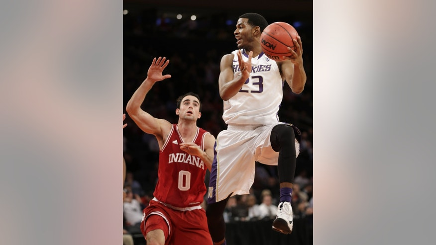 Washington's C.J. Wilcox, right, looks to pass around Indiana's Will Sheehey during the first half of an NCAA college basketball game on Thursday, Nov. 21, 2013, in New York. (AP Photo/Seth Wenig)
