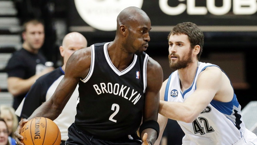 Brooklyn Nets' Kevin Garnett, left, drives around Minnesota Timberwolves' Kevin Love in the first quarter of an NBA basketball game Friday, Nov. 22, 2013, in Minneapolis. (AP Photo/Jim Mone)