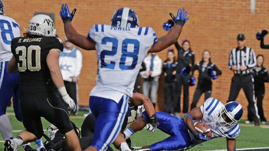 Duke's Jamison Crowder, right, dives into the end zone for a touchdown as Shaquille Powell, center, celebrates and Wake Forest's Hunter Williams (30) looks on during the first half of an NCAA college football game in Winston-Salem, N.C., Saturday, Nov. 23, 2013. (AP Photo/Chuck Burton)