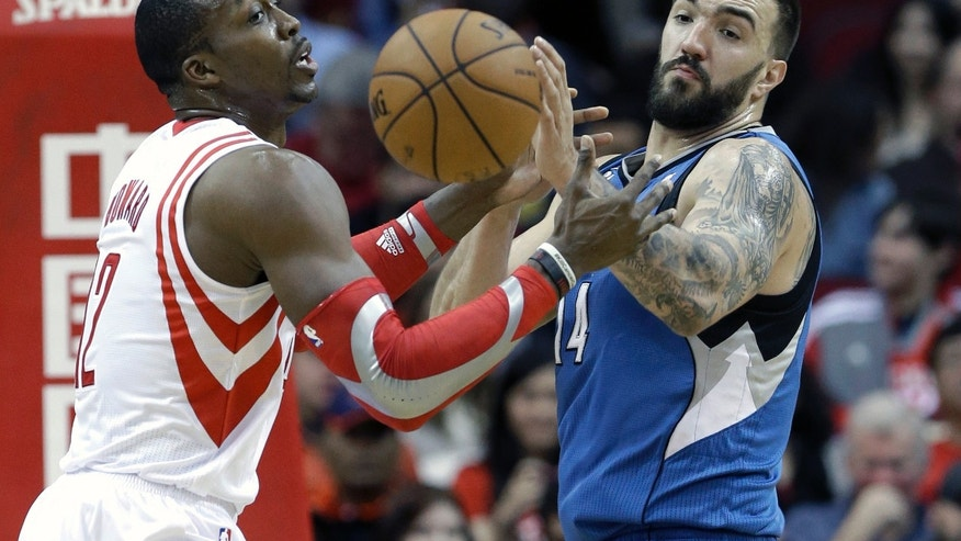 Minnesota Timberwolves' Nikola Pekovic (14) knocks the ball away from Houston Rockets' Dwight Howard (12) in the first half of an NBA basketball game Saturday, Nov. 23, 2013, in Houston. (AP Photo/Pat Sullivan)