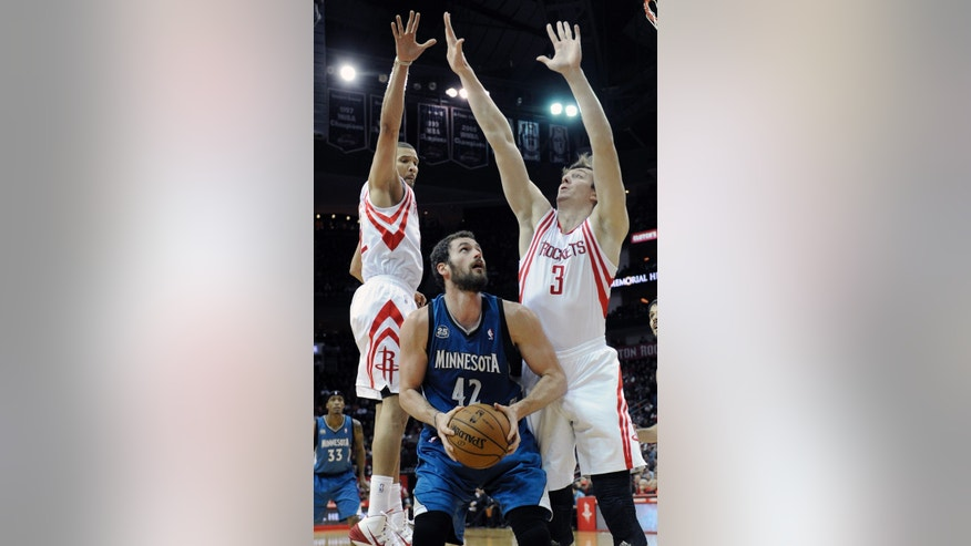 Minnesota Timberwolves' Kevin Love (42) looks for a shot between the defense of Houston Rockets Omer Asik (3) and Francisco Garcia in the first half of an NBA basketball game Saturday, Nov. 23, 2013, in Houston. (AP Photo/Pat Sullivan)