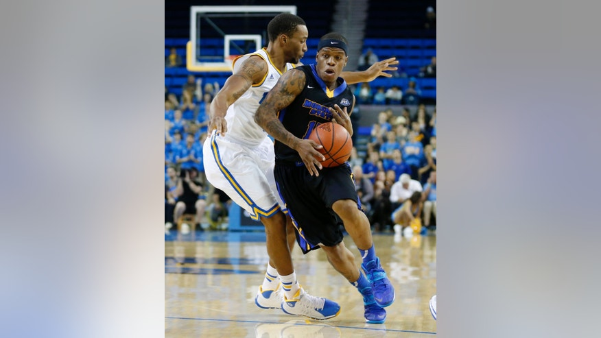 Morehead State's Kareem Storey, right, takes the ball past UCLA's Norman Powell, left, during the first half of a Las Vegas Invitational regional NCAA college basketball game, Friday, Nov. 22, 2013, in Los Angeles. (AP Photo/Danny Moloshok)