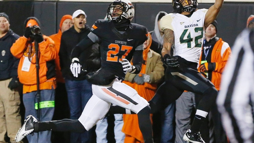 Baylor receiver Levi Norwood (42) can't make the catch on a pass in front of Oklahoma State safety Lyndell Johnson (27) in the second quarter of an NCAA college football game in Stillwater, Okla., Saturday, Nov. 23, 2013. (AP Photo/Sue Ogrocki)