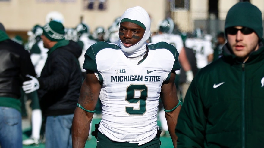 Michigan State safety Isaiah Lewis (9) leaves the field after being ejected for a targeting penalty during the first half of an NCAA football game against Northwesten on Saturday, Nov. 23, 2013, in Evanston, Ill. (AP Photo/Andrew A. Nelles)