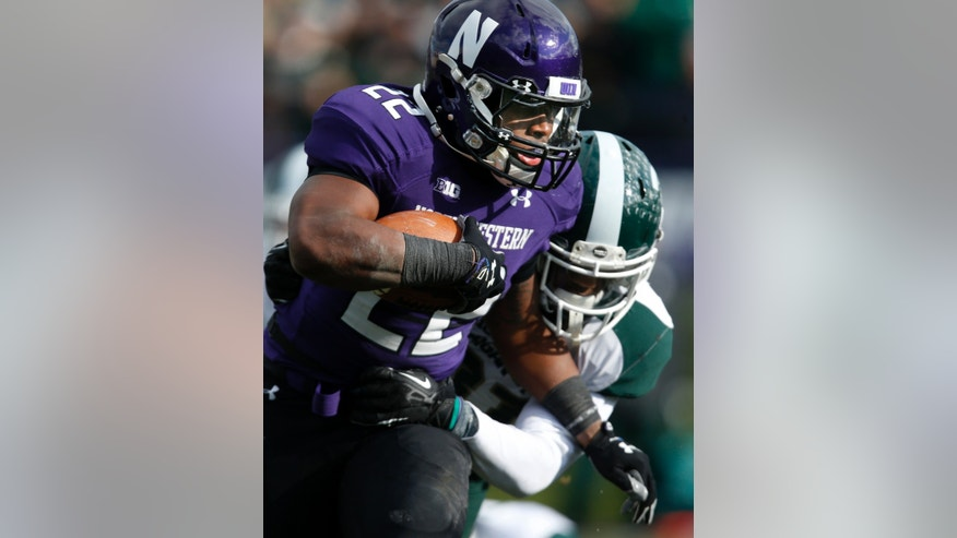 Northwestern running back Treyvon Green (22) takes a hit from Michigan State cornerback Darqueze Dennard (31) during the first half of an NCAA fcollege football game on Saturday, Nov. 23, 2013, in Evanston, Ill. (AP Photo/Andrew A. Nelles)