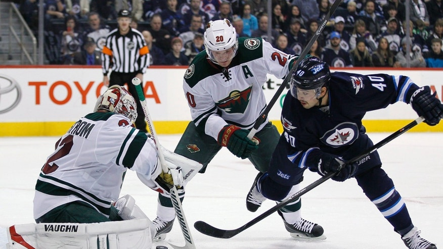 Minnesota Wild's goaltender Niklas Backstrom (32) stops the shot from Winnipeg Jets' Devin Setoguchi (40) as Wild's Ryan Suter (20) forces Setoguchi off the rebound during the second  period of an NHL game in Winnipeg, Manitoba, Saturday, Nov. 23, 2013. (AP Photo/The Canadian Press, John Woods)
