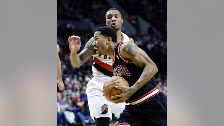 Chicago Bulls guard Derrick Rose, left, drives to the basket past Portland Trail Blazers guard Damian Lillard during the first half of an NBA basketball game in Portland, Ore., Friday, Nov. 22, 2013. (AP Photo/Don Ryan)