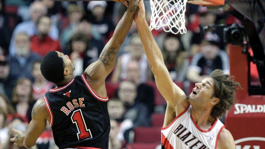 Portland Trail Blazers center Robin Lopez, right, blocks a shot by Chicago Bulls guard Derrick Rose during the first half of an NBA basketball game in Portland, Ore., Friday, Nov. 22, 2013. (AP Photo/Don Ryan)
