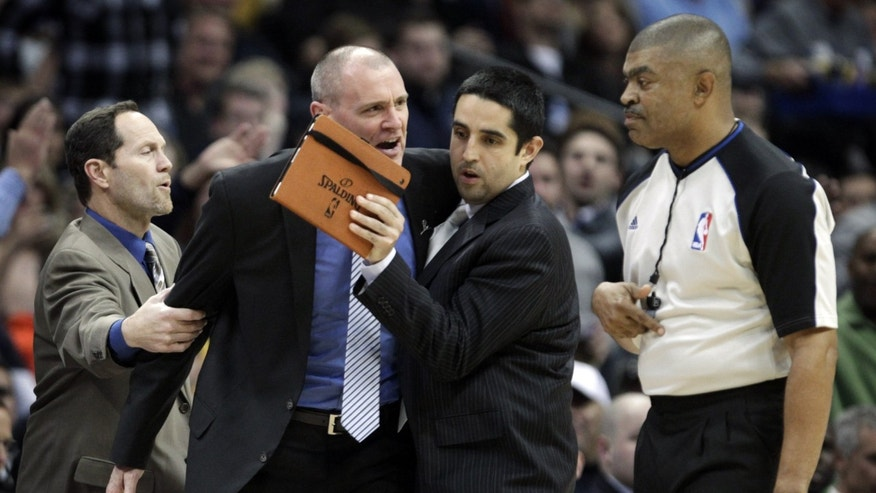 Dallas Mavericks assistant coaches Monte Mathis, left, and Kaleb Canales, third from left, try to separate coach Rick Carlisle from referee Tony Brothers, right, moments before Carlisle was issued a second technical foul and ejected in the second quarter of an NBA basketball game in Denver on Saturday, Nov. 23, 2013. (AP Photo/Joe Mahoney)