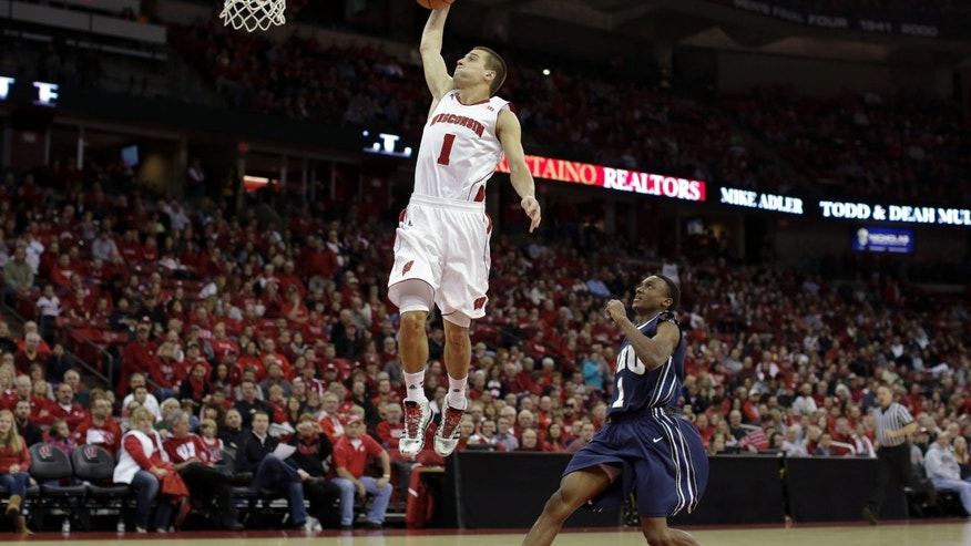 Wisconsin's Ben Brust (1) shoots past Oral Robets' Bobby Word during the second half of an NCAA college basketball game on Saturday, Nov. 23, 2013, in Madison, Wis. Wisconsin won 76-67. (AP Photo/Andy Manis)