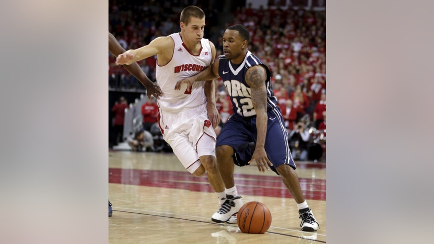 Oral Roberts' D.J. Jackson (12) drives against Wisconsin's Ben Brust during the first half of an NCAA college basketball game on Saturday, Nov. 23, 2013, in Madison, Wis. (AP Photo/Andy Manis)