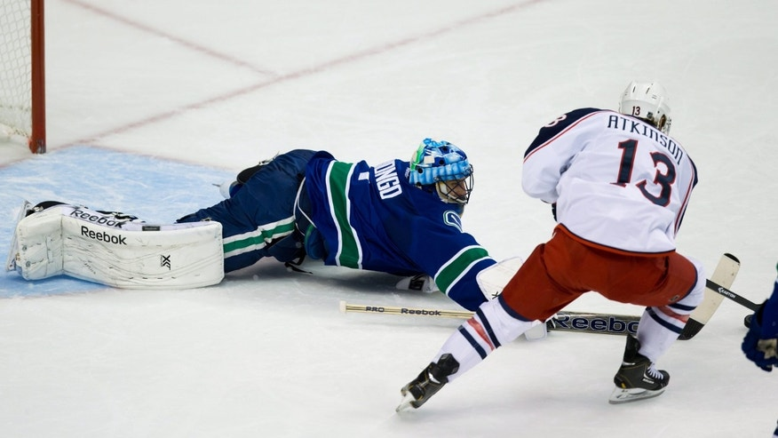 Vancouver Canucks' goalie Roberto Luongo, left, poke-checks the puck off the stick of Columbus Blue Jackets' Cam Atkinson during second period NHL hockey action in Vancouver, British Columbia, on Friday Nov. 22, 2013. (AP Photo/The Canadian Press, Darryl Dyck)