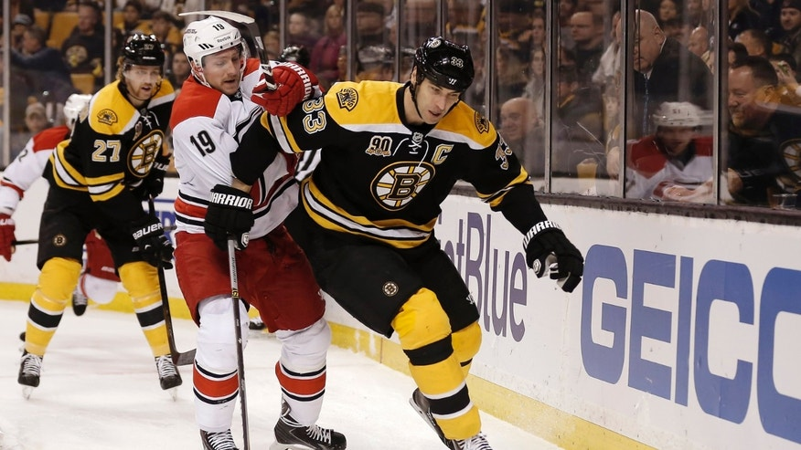 Boston Bruins defenseman Zdeno Chara (33) tries to keep Carolina Hurricanes' Jiri Tlusty (19) from a loose puck during the first period of a NHL hockey game in Boston Saturday, Nov. 23, 2013. (AP Photo/Winslow Townson)
