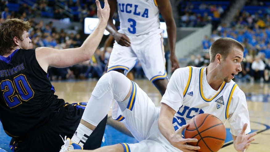UCLA's Travis Wear, right, passes the ball off in front of Morehead State's Chad Posthumus, left, during the first half of a Las Vegas Invitational regional NCAA college basketball game, Friday, Nov. 22, 2013, in Los Angeles. (AP Photo/Danny Moloshok)