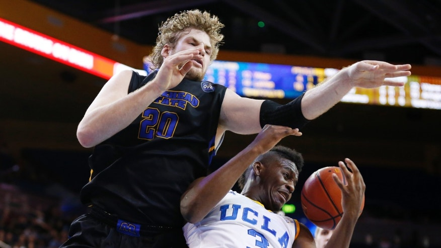 Morehead State's Chad Posthumus, left, fouls UCLA's Jordan Adams, right, on a rebound attempt during the first half of a Las Vegas Invitational regional NCAA college basketball game, Friday, Nov. 22, 2013, in Los Angeles. (AP Photo/Danny Moloshok)