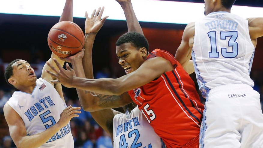 Richmond's Terry Allen (15) runs into North Carolina defenders Marcus Paige (5), Joel James (42) and J.P. Tokoto (13) during the second half of an NCAA college basketball game in the semifinal round of the Basketball Hall of Fame Tip-Off tournament at Mohegan Sun Arena in Uncasville, Conn., Saturday, Nov. 23, 2013. North Carolina won 82-72. (AP Photo/Michael Dwyer)