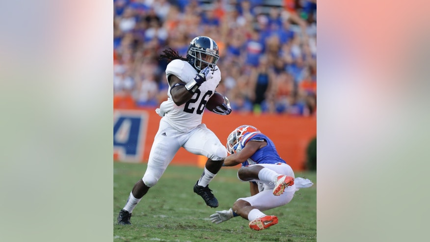 Georgia Southern wide receiver Tray Butler (26) runs past Florida defensive back Cody Riggs during the second half of an NCAA college football game in Gainesville, Fla., Saturday, Nov. 23, 2013.(AP Photo/John Raoux)