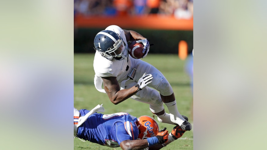 Georgia Southern's Jerick McKinnon (1) is upended by Florida linebacker Jarrad Davis, bottom, during the first half of an NCAA college football game in Gainesville, Fla., Saturday, Nov. 23, 2013.(AP Photo/John Raoux)
