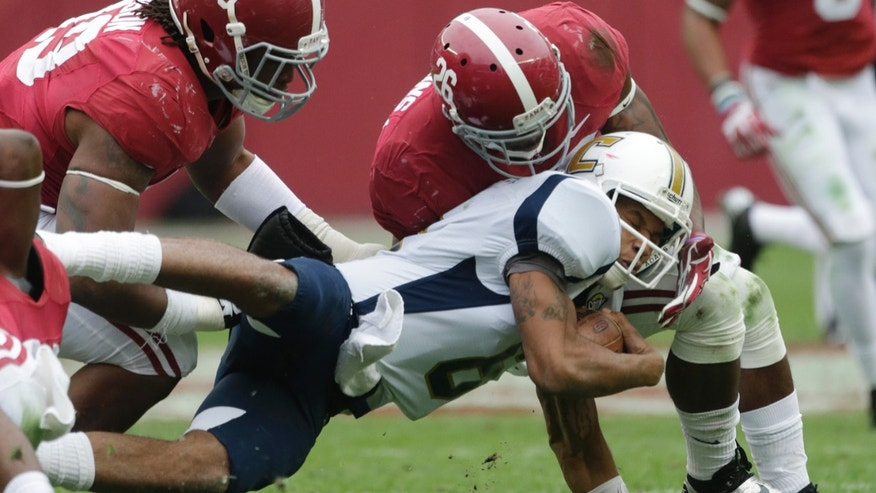 Chattanooga quarterback Terrell Robinson (6) dives for a first down as Alabama defensive back Landon Collins (26) and  defensive lineman Ed Stinson (49) make the tackle during the first half of an NCAA college football game in Tuscaloosa, Ala., Saturday, Nov. 23, 2013. (AP Photo/Dave Martin)