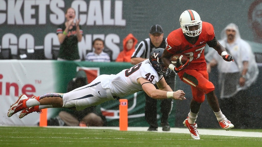 Virginia's Zachary Swanson (49) tries to tackle Miami's Ladarius Guner (37) after he intercepted a pass during the first half of a NCAA college football game in Miami Gardens, Fla., Saturday, Nov. 23, 2013. (AP Photo/J Pat Carter)