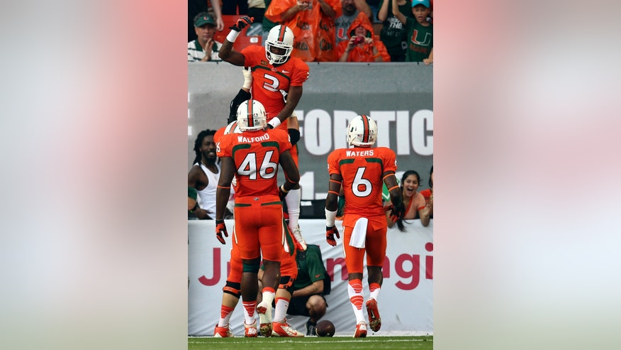 Miami's Clive Walford (46) and Herb Waters (6) celebrate with Stacy Coley (3) after he scored a touchdown during the first half of a NCAA college football game against Virginia in Miami Gardens, Fla., Saturday, Nov. 23, 2013.(AP Photo/J Pat Carter)
