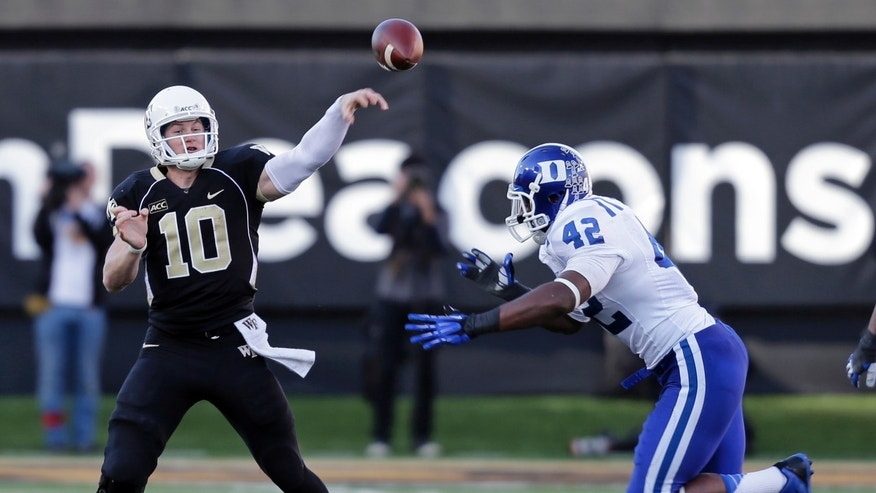 Wake Forest quarterback Tanner Price (10) throws a pass under pressure from Duke defensive end Dezmond Johnson (42) during the second half of an NCAA college football game in Winston-Salem, N.C., Saturday, Nov. 23, 2013. Duke won 28-21. (AP Photo/Chuck Burton)