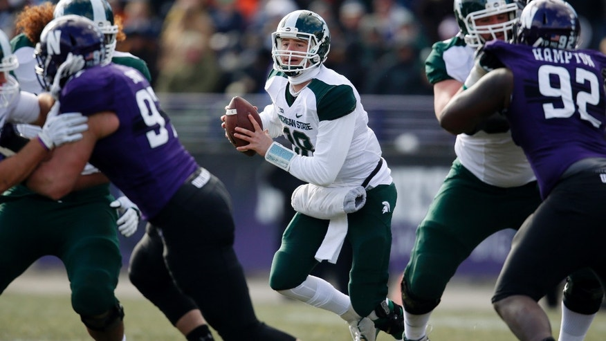 Michigan State quarterback Connor Cook (18) advances against Northwestern during the first half of an NCAA college football game on Saturday, Nov. 23, 2013, in Evanston, Ill. (AP Photo/Andrew A. Nelles)