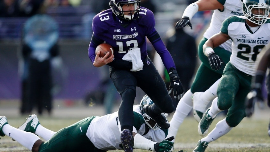 Northwestern quarterback Trevor Siemian (13) leaps over Michigan State defensive end Joel Heath (92) during the second half of an NCAA football game on Saturday, Nov. 23, 2013, in Evanston, Ill. (AP Photo/Andrew A. Nelles)