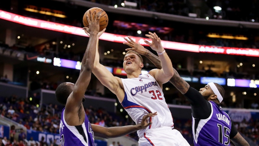 Los Angeles Clippers forward Blake Griffin, middle, shoots between Sacramento Kings forward Luc Richard Mbah a Moute, left, and center DeMarcus Cousins during the first half of an NBA basketball game in Los Angeles, Saturday, Nov. 23, 2013. (AP Photo/Chris Carlson)