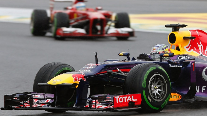 Red Bull driver Sebastian Vettel of Germany steers his car in front of Ferrari driver Fernando Alonso of Spain, during the qualifying at the Interlagos race track in Sao Paulo, Brazil, Saturday, Nov. 23, 2013. The Brazilian Formula One Grand Prix will take place on Sunday. (AP Photo/Andre Penner)
