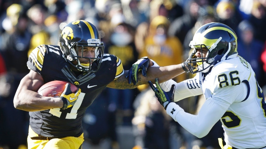 Iowa's Kevonte Martin-Manley runs from Michigan's Jehu Chesson (86) during a punt return in the first half of an NCAA college football game, Saturday, Nov. 23, 2013, in Iowa City, Iowa. (AP Photo/Charlie Neibergall)