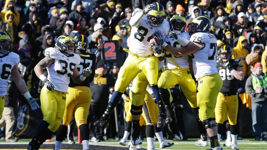 Michigan tight end A.J. Williams, center, celebrates with teammates after catching a 2-yard touchdown pass during the first half of an NCAA college football game against Iowa, Saturday, Nov. 23, 2013, in Iowa City, Iowa. (AP Photo/Charlie Neibergall)