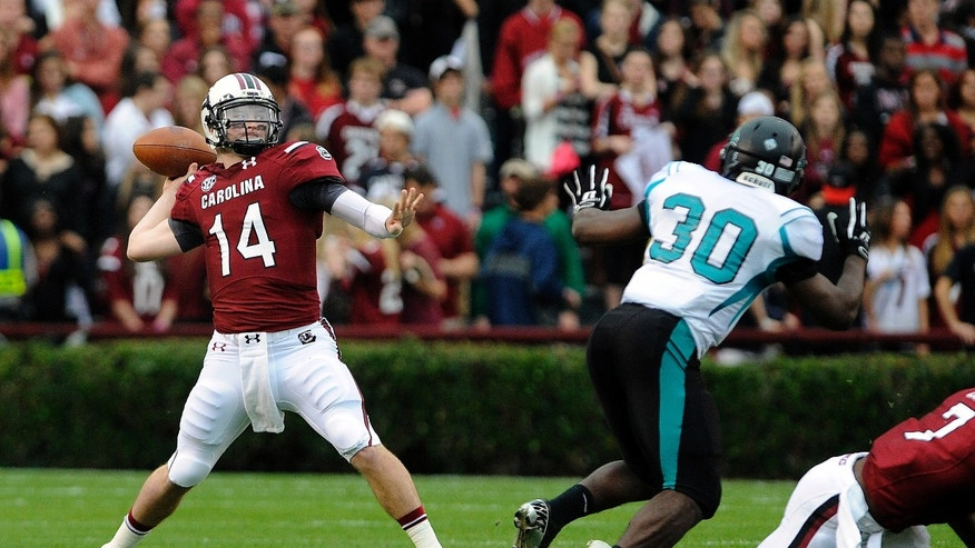 South Carolina quarterback Connor Shaw (14) passes down field during the first half of an NCAA college football game against Coastal Carolina, Saturday, Nov. 23, 2013 in Columbia, S.C. (AP Photo/Stephen Morton)