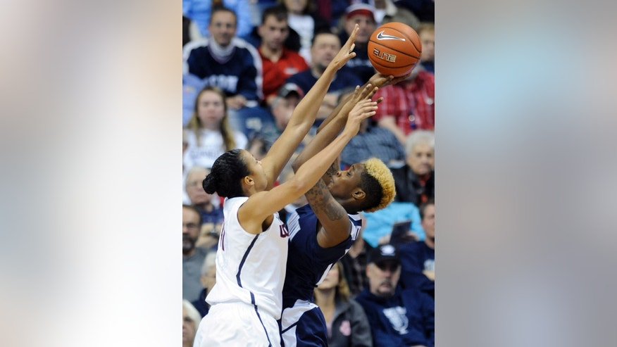 Connecticut's Kiah Stokes (41) guards Monmouth's Christina Mitchell  during the first half of an NCAA college basketball game, in Storrs, Conn., on Saturday, Nov. 23, 2013. (AP Photo/Fred Beckham)