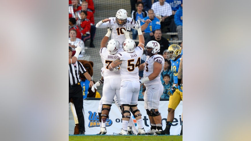 Arizona State quarterback Taylor Kelly, top, celebrates his touchdown with offensive linesman Jamil Douglas, left, offensive linesman Tyler Sulka and offensive linesman Vi Teofilo as UCLA cornerback Fabian Moreau looks on during the first half an NCAA college football game, Saturday, Nov. 23, 2013, in Pasadena, Calif. (AP Photo/Mark J. Terrill)