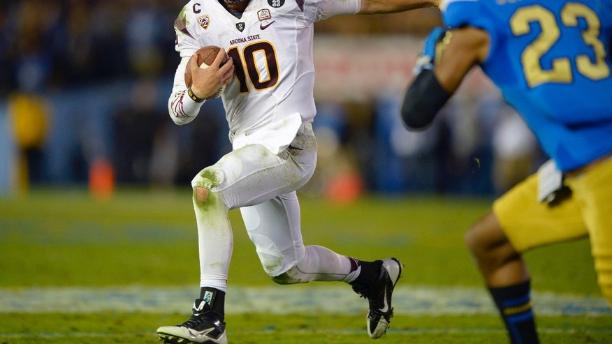 Arizona State quarterback Taylor Kelly, left, runs the ball as UCLA cornerback Anthony Jefferson defends during the first half an NCAA college football game, Saturday, Nov. 23, 2013, in Pasadena, Calif. (AP Photo/Mark J. Terrill)