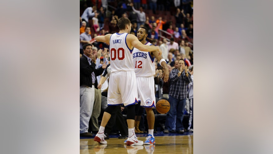Philadelphia 76ers' Evan Turner (12) and Spencer Hawes (00) celebrate after winning an NBA basketball game against the Milwaukee Bucks, Friday, Nov. 22, 2013, in Philadelphia. Philadelphia won 115-107 in overtime. (AP Photo/Matt Slocum)
