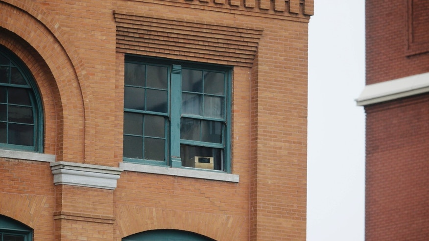 The window, center with box, at the Texas School Book Depository building where Lee Harvey Oswald stood to shoot at John F. Kennedy is seen before a ceremony to mark the 50th anniversary of Kennedy's  assassination, Friday, Nov. 22, 2013, at Dealey Plaza in Dallas. President Kennedy's motorcade was passing through Dealey Plaza when shots rang out on Nov. 22, 1963. (AP Photo/Tony Gutierrez)