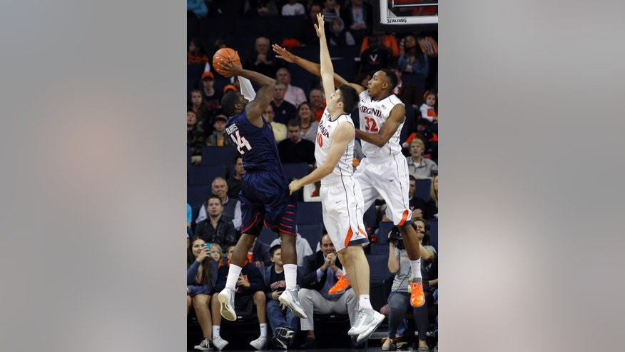 Virginia's Mike Tobey (10) and Darion Atkins (32) defend Liberty's Antwan Burrus (24) as he shoots the ball during the first half of an NCAA college basketball game Saturday, Nov. 23, 2013, in Charlottesville, Va. (AP Photo/Andrew Shurtleff)