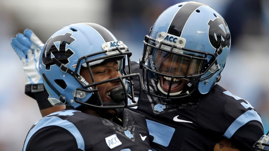 North Carolina's T.J. Thorpe, right, and Quinshad Davis (14) celebrate Davis' touchdown against Old Dominion during the first half of an NCAA college football game in Chapel Hill, N.C., Saturday, Nov. 23, 2013. North Carolina won 80-20.  (AP Photo/Gerry Broome)