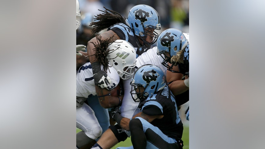 North Carolina's Tim Jackson (93) and Malik Simmons  (11) tackle Old Dominion's Cam Boyd during the first half of an NCAA college football game in Chapel Hill, N.C., Saturday, Nov. 23, 2013. (AP Photo/Gerry Broome)