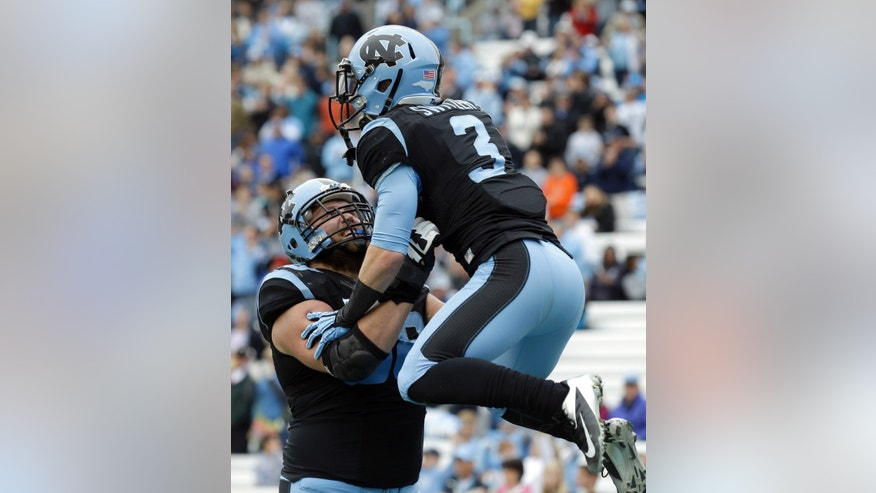 North Carolina's James Hurst lifts Ryan Switzer (3) following Switzer's touchdown against Old Dominion during the first half of an NCAA college football game in Chapel Hill, N.C., Saturday, Nov. 23, 2013. (AP Photo/Gerry Broome)