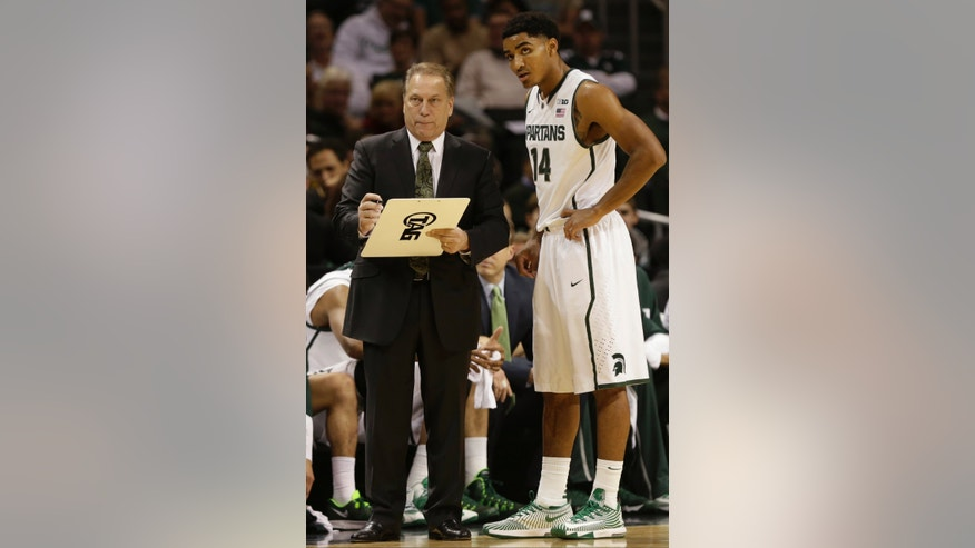 Michigan State head coach Tom Izzo, left, talks to Gary Harris (14) during the first half of the championship game against the Oklahoma in the Coaches vs. Cancer NCAA college basketball game on Saturday, Nov. 23, 2013, in New York. (AP Photo/Frank Franklin II)