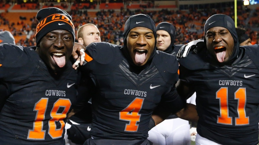 Oklahoma State's Deion Imade (18), Justin Gilbert (4) and Shaun Lewis (11) celebrate after defeating Baylor in an NCAA college football game in Stillwater, Okla., Saturday, Nov. 23, 2013. Oklahoma State won 49-17. (AP Photo/Sue Ogrocki)