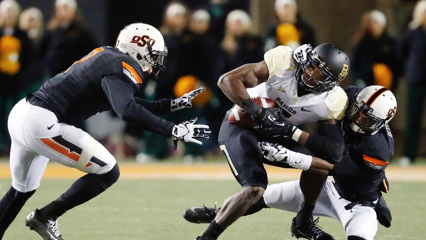 Baylor wide receiver Antwan Goodley (5) is tackled by Oklahoma State cornerback Kevin Peterson, right, in the second quarter of an NCAA college football game in Stillwater, Okla., Saturday, Nov. 23, 2013. (AP Photo/Sue Ogrocki)